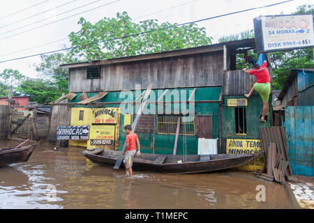 2015 flooding in Brazilian Amazon, woman climbs her house at Taquari district, Rio Branco city, Acre State. Floods have been affecting thousands of people in the state of Acre, northern Brazil, since 23 February 2015, when some of the state's rivers, in particular the Acre river, overflowed. Further heavy rainfall has forced river levels higher still, and on 03 March 2015 Brazil's federal government declared a state of emergency in Acre State, where current flood situation has been described as the worst in 132 years. One of the worst affected areas is the state capital, Rio Branco, where leve - Stock Photo