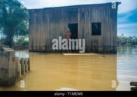 2015 flooding in Brazilian Amazon, normal daily life, man shaves in front of flooded house at Taquari district, Rio Branco city, Acre State. Floods have been affecting thousands of people in the state of Acre, northern Brazil, since 23 February 2015, when some of the state's rivers, in particular the Acre river, overflowed. Further heavy rainfall has forced river levels higher still, and on 03 March 2015 Brazil's federal government declared a state of emergency in Acre State, where current flood situation has been described as the worst in 132 years. - Stock Photo