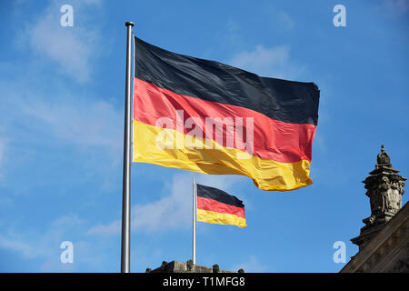 05.03.2019, Berlin, Berlin, Germany - The German national flag on a flagpole in front of and on the Reichstag building. 00R190305D148CAROEX.JPG [MODEL - Stock Photo