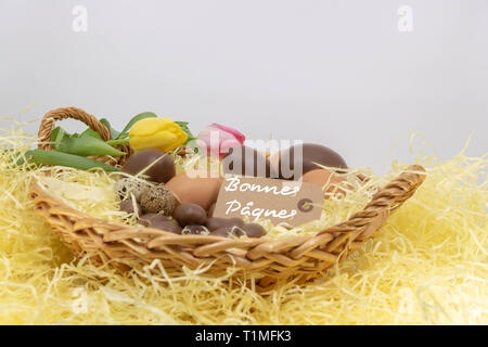 Joyeuses Pâques is Happy Easter written in French on a label in a wicker basket filled with eggs and tulips - Stock Photo