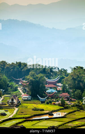 A Torajan highland village with traditional houses set in rice fields in South Sulawesi, Indonesia - Stock Photo