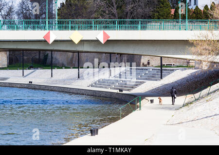 Woman walking dog on the bank of River Raab (Rába) in Gyor, Hungary. Bridge over the river with sighs for ships. - Stock Photo