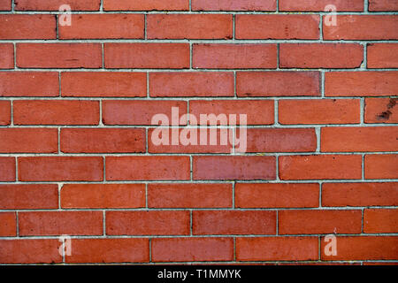 Closeup Section of plain wall 1950's red brick wall laid in courses of bricks - Stock Photo