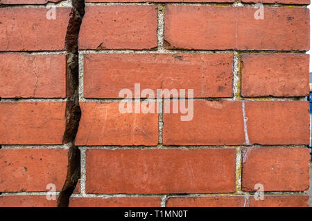 Really big 12.7mm or 1/2 inch crack going vertically down splitting a red brick wall into two - Stock Photo