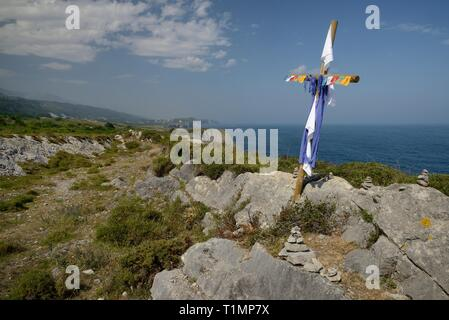 Camino de Santiago coastal route, marked with piles of stones and a cross left by pilgrims, along the cliff edge, near Buelna,  Asturias, Spain. - Stock Photo