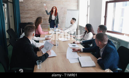 People at the business conference. Annoyed woman chief throws crumpled paper - Stock Photo