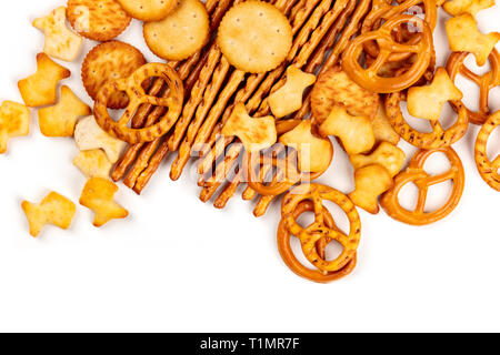 Many salty crackers, sticks, pretzels, and gold fishes, shot from the top on a white background with copy space. Party snacks mix banner - Stock Photo