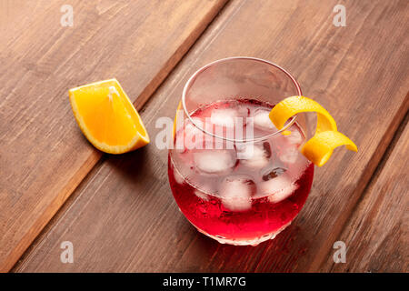 A vibrant cocktail with campari and an orange curl garnish, with ice cubes and an orange slice, on a dark rustic wooden background - Stock Photo