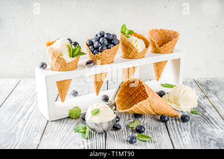 White vanilla ice cream balls with ice cream cones, spoon, fresh blueberry berries and mint leaves, rustic wooden background copy space - Stock Photo