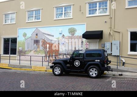 Police car parked in front of a building mural in downtown Brooksville, Florida - Stock Photo