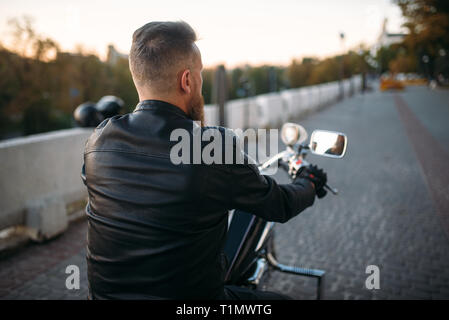 Biker poses on chopper in city, front view - Stock Photo