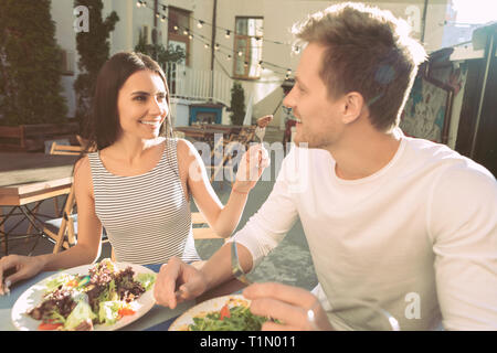 Beaming pleasant couple eating healthy food on summer terrace - Stock Photo