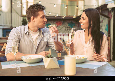 Pleasant handsome man carrying oyster shell and looking on his woman - Stock Photo