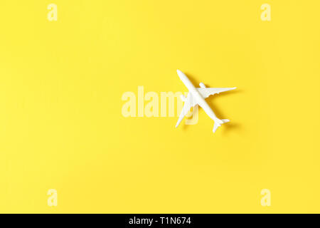 White toy airplane on a yellow background with copy space - Stock Photo