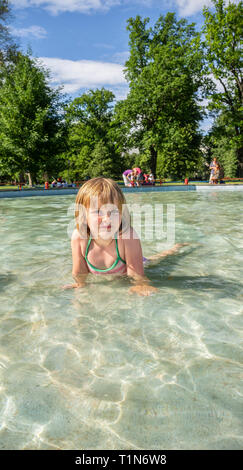 5 year old girl bathing in a swimming pool outdoors in the summer. - Stock Photo