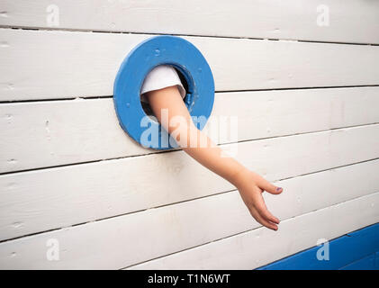 Child holding out a helping hand - Stock Photo