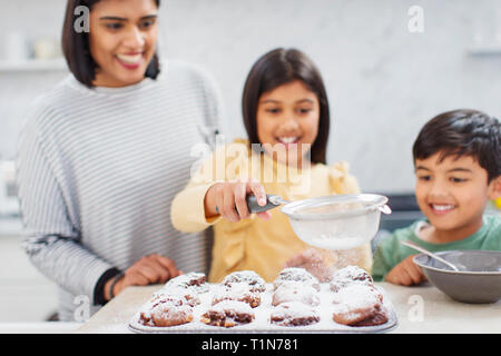Mother and children baking muffins in kitchen - Stock Photo