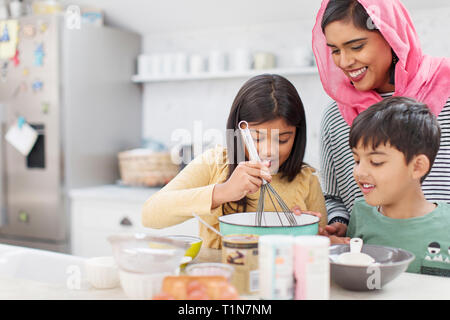 Mother in hijab baking with children in kitchen - Stock Photo