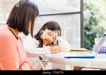 Mother at laptop watching daughter doing homework at table - Stock Photo