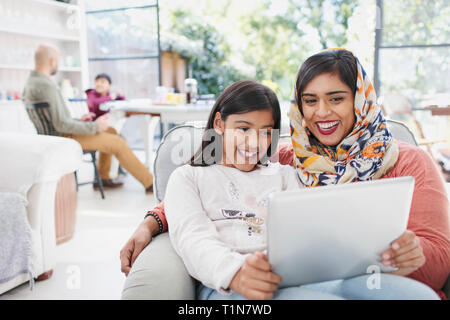 Happy mother in hijab and daughter using digital tablet - Stock Photo