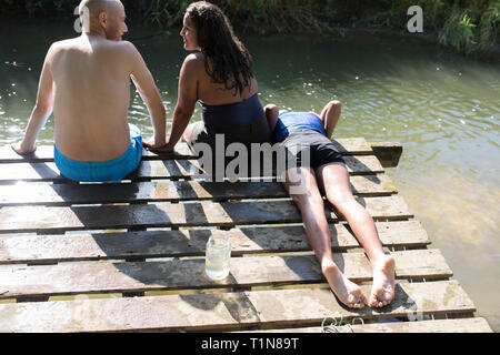 Family relaxing on dock at sunny riverside - Stock Photo