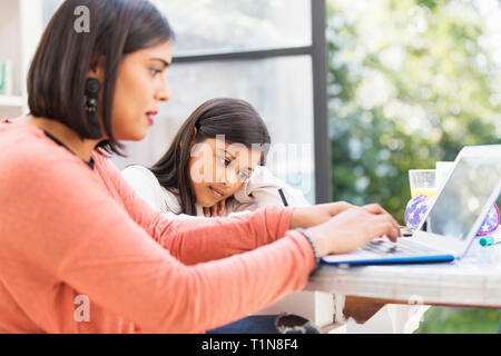 Mother and daughter using laptop, doing homework at table - Stock Photo