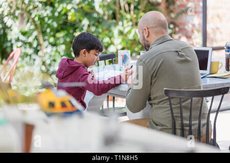 Father and son coloring at table - Stock Photo