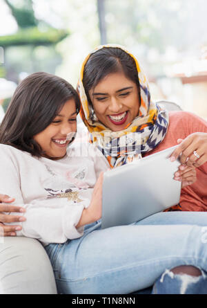 Laughing, happy mother in hijab and daughter using digital tablet - Stock Photo