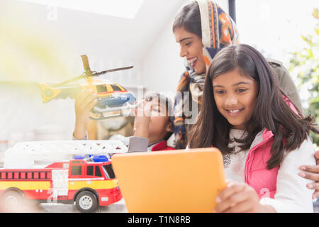 Mother in hijab watching children playing with toys and digital tablet - Stock Photo