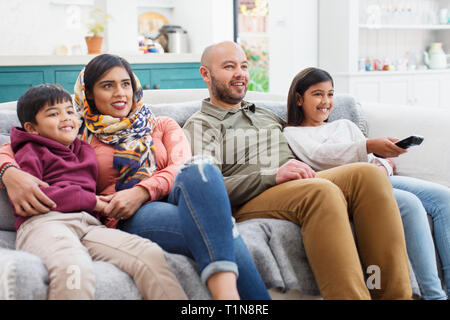 Family watching TV on living room sofa - Stock Photo