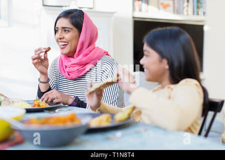 Happy mother in hijab and daughter eating dinner - Stock Photo