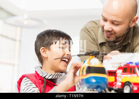 Father and son playing with helicopter and fire engine toys - Stock Photo