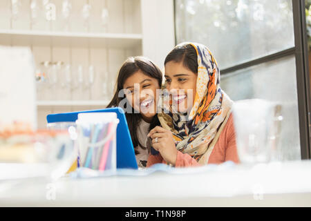 Happy mother in hijab and daughter using laptop - Stock Photo
