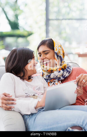 Happy mother in hijab using digital tablet with daughter - Stock Photo