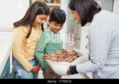 Mother and children baking chocolate muffins - Stock Photo