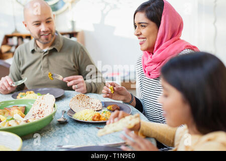 Happy woman in hijab eating dinner with family at table - Stock Photo