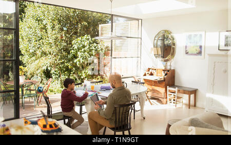 Father and son using digital tablet and coloring at dining table - Stock Photo
