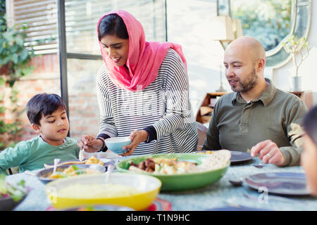 Mother in hijab serving dinner to family at table - Stock Photo