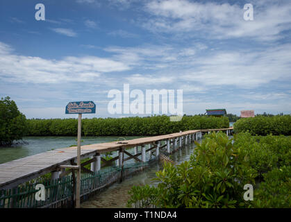 Kelapa Island, Indonesia - December 24, 2017 : Joka Landro, wooden bridge that leads to two floating cottage in the middle of mangrove forest - Stock Photo