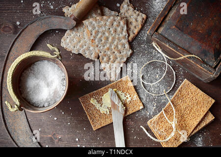 Rye crackers, wooden knife,old wooden box for lunch, old rusty sickle and copper cup with salt on the brown wooden board - Stock Photo