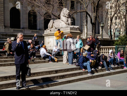 A businessman in a suit holding a briefcase talks on his phone in front of NYC public Library on 5th Ave. People sit on steps behind. Mar 2018 - Stock Photo