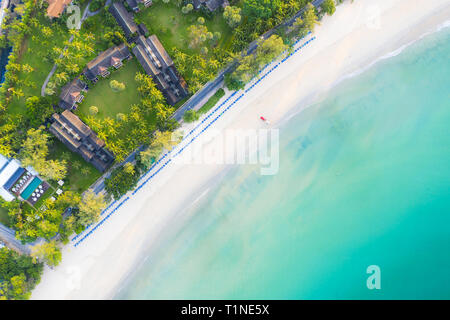 Aerial view of sandy beach with tourists swimming in beautiful clear sea water in Phuket, Thailand.