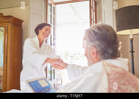 Happy, affectionate couple in bathrobes in hotel room - Stock Photo