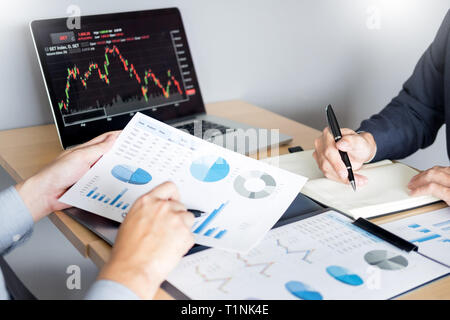 Businessmen talking about stock market invest trading online analysis discussing financial graph  for investment purposes discussion in traders office - Stock Photo