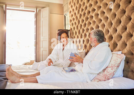Mature couple in bathrobes on hotel bed - Stock Photo