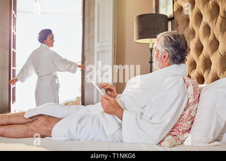 Mature couple in bathrobes relaxing in hotel room - Stock Photo