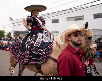 Young woman dressed in traditional charreada clothing waves while riding a horse in the annual Washington's Birthday Celebration parade in Laredo TX - Stock Photo