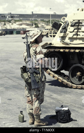 29th October 2003 A female New Zealand national, serving as a U.S. Army soldier, stands next to an M88 recovery vehicle, an M16A2 rifle over her shoulder, in the new port in Mogadishu, Somalia. - Stock Photo