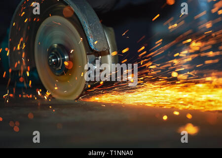 Close-up of the rotation of the disk angle grinder during operation. Bright sparks from metal cutting. Dark industrial background - Stock Photo