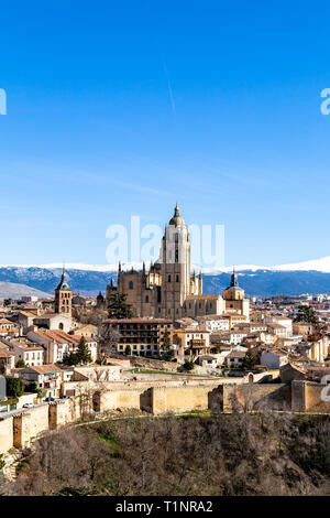 Segovia, Spain: view from Juan II tower in Winter time of the Alcazar of the old town of Segovia and the Cathedral with the snow capped Sierra de Guad - Stock Photo